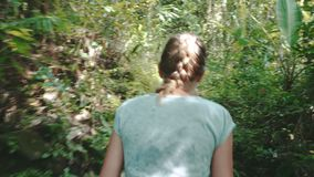 Woman walking in rain forest jungle stock video