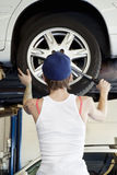 Back view of young female mechanic working on lifted car's tire in automobile repair shop Stock Image