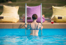Back view young female in swimsuit coming out from the water of a swimming pool at the resort. Near stands a glass with a drink Royalty Free Stock Image
