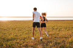 Back view of young fitness man and woman doing jogging. Back view of young fitness men and women doing jogging sport outdoors royalty free stock photo