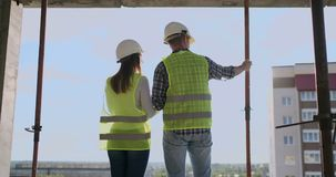 Back view young foreman and engineer checking the blueprint and talking about construction project with commitment to. Success at construction site stock footage