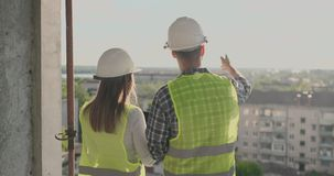 Back view young foreman and engineer checking the blueprint and talking about construction project with commitment to. Success at construction site stock video