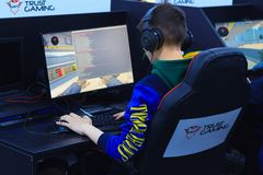 Back view of young gamer playing video game. Moscow, Russia, April, 2018: Back view of young gamer on the armchair in headphone playing video game on a e-sport royalty free stock photography