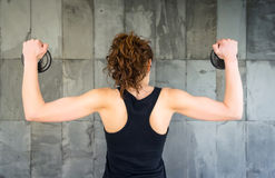 Back view of young girl lifting dumbbell discs Stock Photo