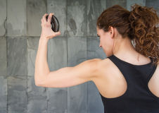 Back view of young girl lifting dumbbell discs Royalty Free Stock Images