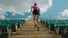 Back view of a young girl running upstairs at a stadium. Slow motion shot. The camera follows the athlete to the top stock video footage