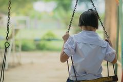 Back view of young girl sit on swing for wait her friend at the stock photo