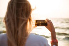 Back view of a young girl taking a picture of a sunset. At the beach with mobile phone Stock Photography
