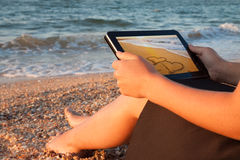 Back view of a young girl towards her tablet with love picture on beach Stock Images