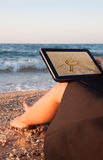 Back view of a young girl towards her tablet with sun picture on beach stock photo