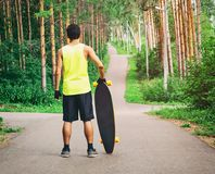 Guy staying with longboard in park. Back view of young guy staying with longboard or skateboard on the road ready to skate in park Stock Images