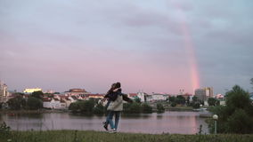 Back view of young happy couple running on the shore of the river on sunset. Man and woman having fun together. Beautiful city view and rainbow. Romantic date stock video