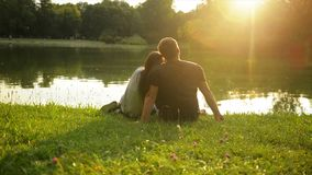 Back View of the Young Happy Family Kissing During Beautiful Sunset Sitting near the Lake in the City Park. stock video footage