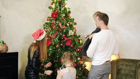 Back view of young happy joyful family of a mother dressed in Santa Claus hat, father and two cute daughters decorating. Christmas tree together at home. Slow stock footage