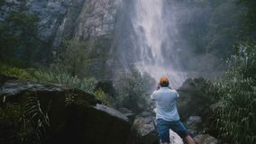 Back view young happy tourist man taking smartphone photo at large scenic Sri Lanka tropical jungle waterfall. Excited male traveler enjoying amazing stock video