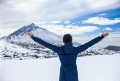 Back view of young happy woman with hands up enjoying snow mount stock photo