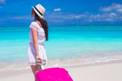 Back view of young happy woman with large luggage on tropical beach Stock Image