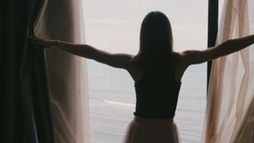 Back view young happy woman walks to open dark hotel apartment room window curtains, enjoy epic sea view slow motion.