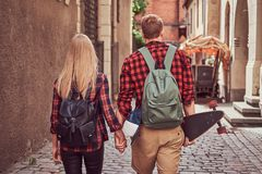 Back view of a young hipster couple, handsome skater and his girlfriend, holding hands, walking around a old narrow. Back view of a young hipster couple stock images