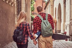 Back view of a young hipster couple, handsome skater and his girlfriend, holding hands, walking around a old narrow. Back view of a young hipster couple stock image