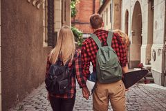 Back view of a young hipster couple, handsome skater and his girlfriend, holding hands, walking around a old narrow. Back view of a young hipster couple stock photos