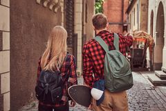 Back view of a young hipster couple, handsome skater and his girlfriend, holding hands, walking around a old narrow. Back view of a young hipster couple stock photography