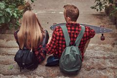 Back view of a young hipster couple, sitting on steps in a park. Royalty Free Stock Photography