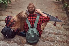 Back view of a young hipster couple, sitting on steps in a park. Royalty Free Stock Image