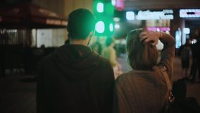 Back view of young hipster couple standing in city centre and listening the concert, musician performance in the evening. Back view of young hipster couple stock video footage