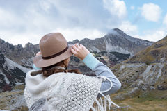 Back view of young lady with hat and warm poncho on mountain lan Stock Photos
