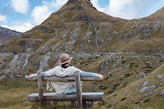 Back view of young lady with hat and warm poncho on mountain lan Stock Images