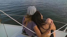 Back view of young lesbian family enjoying sunset on sailboat. Happy people on vacation. lgbt, gay couple, summer holidays stock video footage