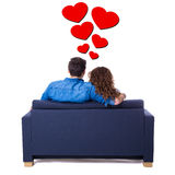 Back view of young lovely couple sitting on sofa isolated on whi Royalty Free Stock Images
