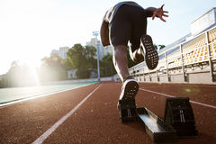 Back view of a young male athlete launching off the start line Royalty Free Stock Photo