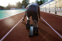 Back view of a young male athlete at starting block. On running track Royalty Free Stock Photos