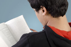 Back view of young male reading book Royalty Free Stock Images