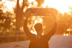 Back view of a male teenager guy holding skateboard. Back view of a young male teenager guy holding skateboard on shoulders and looking at sunset outdoors Royalty Free Stock Images