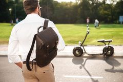 Back view of young man with backpack posing near motorbike Royalty Free Stock Image
