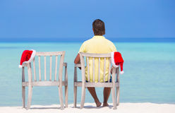 Back view of young man on beach chair with santa Royalty Free Stock Photos