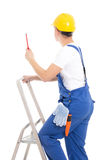 Back view of young man builder in blue coveralls with screwdrive Royalty Free Stock Image