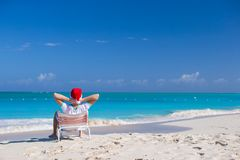 Back view of young man in Christmas hat at beach Stock Images