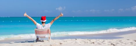 Back view of young man in Christmas hat at beach Stock Photos