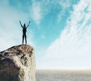 Winner and sports concept. Back view of young man on cliff celebrating victory. Sky background.  Winner and sports concept stock image