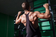Back view of young man doing pull ups Stock Image