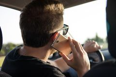 Back view of young man driving a car and talks on the smart phone stock image