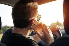 Back view of young man driving a car and talks on the smart phone royalty free stock photos