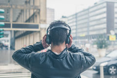 Back view of a young man with headphones posing in the city stre Royalty Free Stock Images