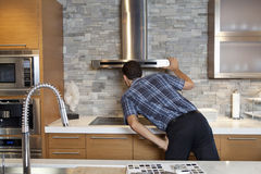 Back view of young man looking at chimney in model home kitchen Stock Photos