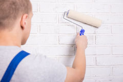 Back view of young man painter in workwear painting brick wall w Royalty Free Stock Images