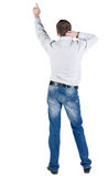 Back view of young man pointing at wall. Royalty Free Stock Photos
